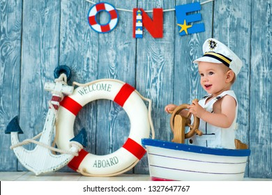 Photoshoot for a boy of one year. Little sea captain, sailor on toy ship with steering wheel. Sea anchor and lifebuoy on gray wooden background