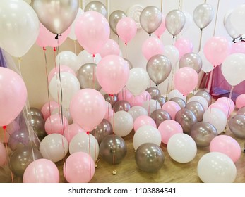 A photostudio decorated with a lot of balloons of white, pink and silvery colors. Gently, stylishly and professionally