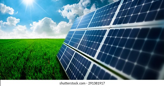 Photovoltaic ecological modules on green grass valley against of sun and cloudy sky