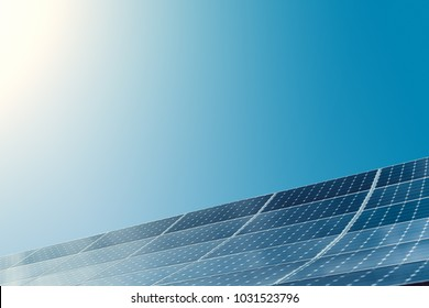 Photovoltaic modules of huge solar panels with clear blue sky and sun on background