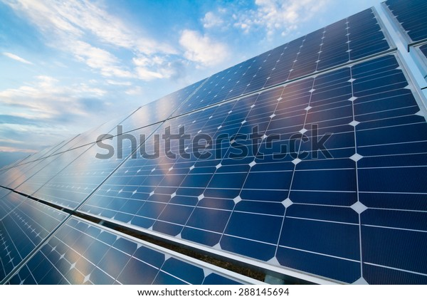 Photovoltaic modules reflect sunset light and clouds