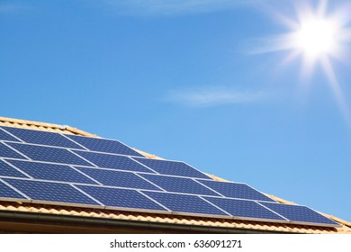 Photovoltaic on the roof of a residential building for alternative energy production in front of amazing blue sky with sunshine, picture with copyspace