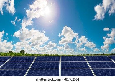 photovoltaic panel with sun shining on blue cloudy sky country background