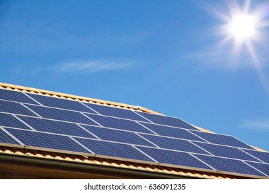Photovoltaic panels on the roof of a residential building for alternative energy production in front of amazing blue sky with sunshine, picture with copy space