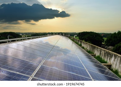 Photovoltaic roof with reflection of the Sun and clouds on the surface.