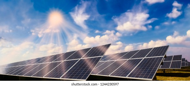 Photovoltaic system with solar modules and bright sun against a blue sky