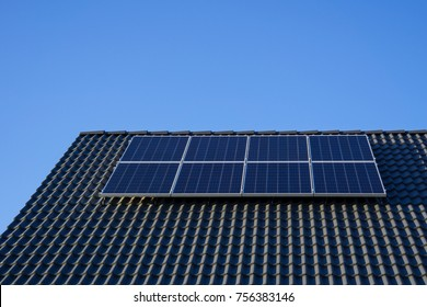 Photovoltaics on roof of new build house with blue sky