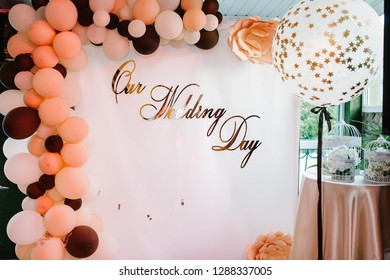 Photo-wall with text our wedding day. Wedding photo zone with balloons and free space. Colorful balloons background, brown, white, gold. Holiday concept. Wedding ceremony with beautiful decoration.