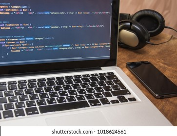 Php code on laptop's display with cellphone and earphones on working place