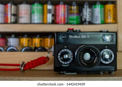 Phrae Thailand : 5/Jul/2019 : Rollei 35T Vintage Camera Once It Was A Smallest 35mm Film Camera in The World with a Background of Camera 35mm Films Kodak Fujifilm Lomography Agfa Vista