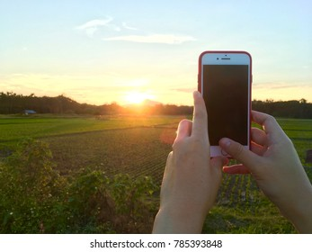 PHRAE, THAILAND - JAN 2, 2018 : Woman's hand holding the phone and take a photo of the sun and mountain in Thailand by the camera app on an Apple iPhone 7 Red.