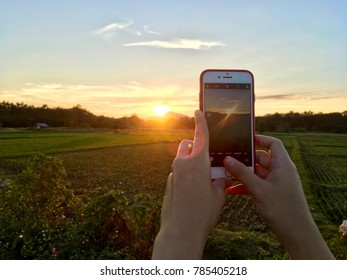 PHRAE, THAILAND - JAN 2, 2018 : Woman's hand holding the phone and take a photo of mountain and sunset in  Thailand by the camera app on an Apple iPhone 7 RED.