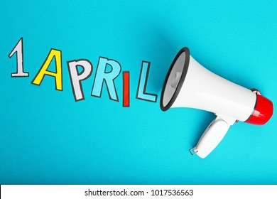 "Phrase ""1 April"" and megaphone on color background. Fool's day celebration"