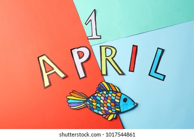 """Phrase """"1 April"""" and paper fish on color background. Fool's day celebration"""