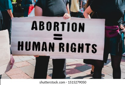 """The phrase """" Abortion = human rights """" drawn on a carton banner in hand. Movement against the prohibition on abortion. A girl holds a cardboard with an inscription. Women's rights protest. Rally"""