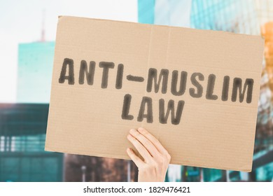 """The phrase """" Anti-muslim law """" on a banner in men's hand with blurred background. Equality. Legislation. Law. Policy. Rules. Protest. Illegal. Ban. Restrictions. Equal"""