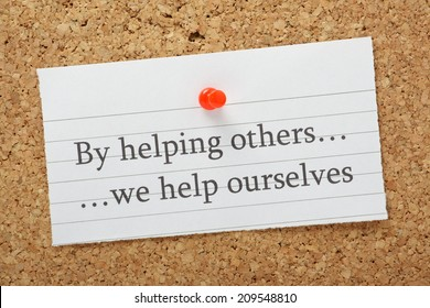 The phrase By helping others we help ourselves typed on a piece of lined paper pinned to a cork notice board