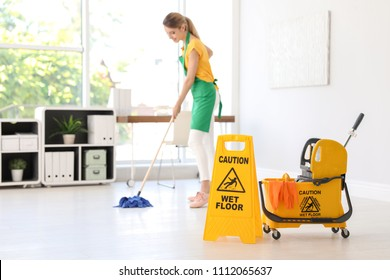 "Phrase ""CAUTION WET FLOOR"" on safety sign, mop bucket with cleaning supplies and young woman on background"