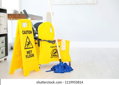 "Phrase ""CAUTION WET FLOOR"" on safety sign and mop bucket with cleaning supplies, indoors"