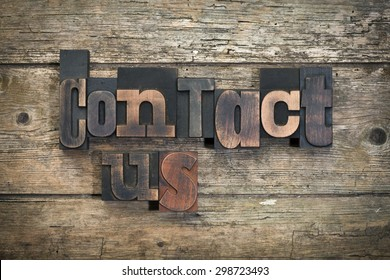 "phrase ""contact us"" written with vintage letterpress printing blocks on rustic wood background"