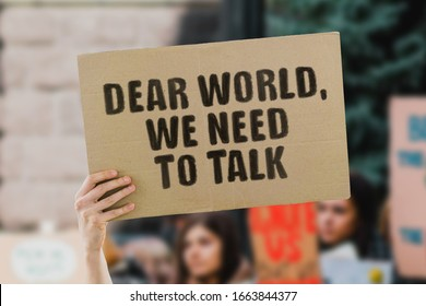 """The phrase """" Dear world, we need to talk """" on a banner in men's hand. Human holds a cardboard with an inscription. Environment pollution. Climate change. Cataclysm. Global warming. Earth. Flooding"""