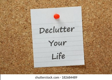 The phrase declutter your life typed on lined paper and pinned to a cork notice board. The process of removing unnecessary distraction drives productivity and efficiency at work and at home.