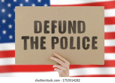 """The phrase """" Defund the police """" on a banner in men's hand with blurred American flag on the background. Violence against black. Fight. Police reform. Occupation. Job. Protest. Brutality. Equality"""