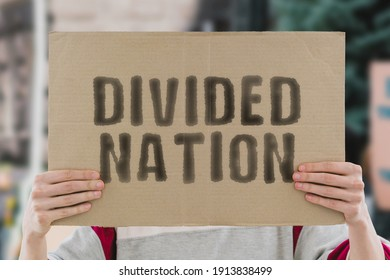 """The phrase """" Divided nation """" on a banner in men's hand with blurred background. Politics. Society. Split. Separation. Problem. Social issue. Confrontation. Protest. Conflict"""