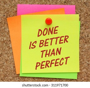 The phrase Done Is Better Than Perfect in red text on a yellow sticky note pinned to a cork notice board as a reminder it is sometimes better to get a product to market than waiting for perfection.