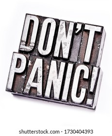 """The phrase """"Don't Panic"""" in letterpress type. Cross processed, narrow focus."""