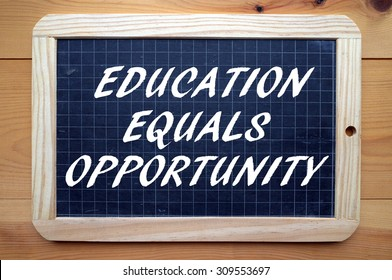 The phrase Education Equals Opportunity in white text on a slate blackboard as a reminder that qualifications lead to work