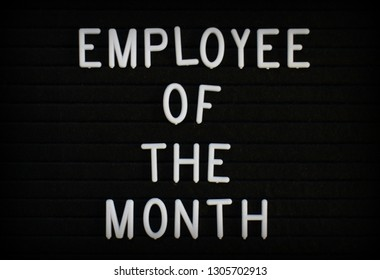 The phrase Employee Of The Month in white plastic letters on a notice board
