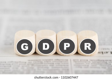 The phrase GDPR on cubes on newspaper. GDPR: General Data Protection Regulation