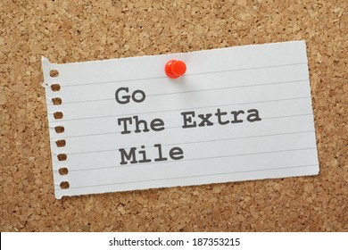 The phrase Go The Extra Mile typed on a piece of lined note paper and pinned to a cork notice board