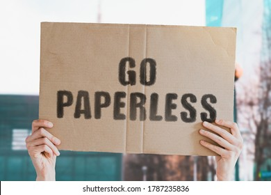 """The phrase """" Go paperless """" on a banner in men's hand with blurred background. Human impact on the environment. Environmental degradation. Nature. Forest. Trees. Modern technology"""