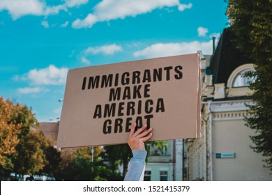 "The phrase "" Immigrants Make America Great "" on a carton banner in men's hand. Human holds a cardboard with an inscription. Immigration. Protest"
