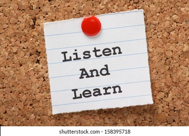The phrase Listen and Learn  typed onto a scrap of lined paper and pinned to a cork notice board. This is the key to success in education and learning new skills for the workplace.