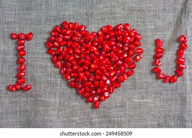 the phrase I love you  from pomegranate seeds on a cloth background