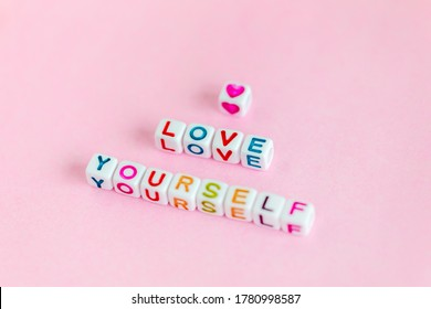 """Phrase """"Love yourself"""" made out of beads on pastel pink background"""