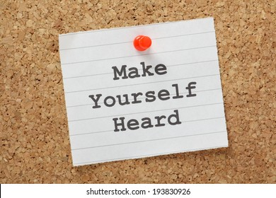 The phrase Make Yourself Heard typed on a piece of lined paper and pinned to a cork notice board