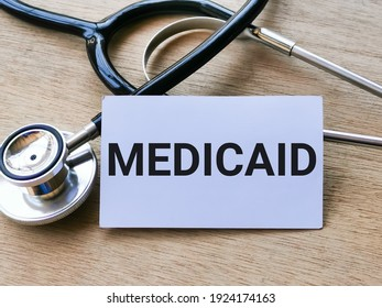 Phrase MEDICAID written on white card with stethoscope. Medical and health concept.