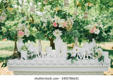 """The phrase """"Mr & Mrs"""" in a wedding decor on a white fireplace surrounded by vases of flowers"""