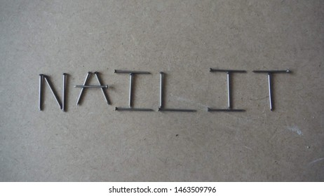 the phrase nail it spelt out in words using steel nails / pins on a block board background.