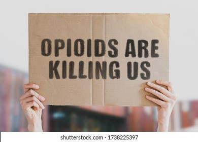 """The phrase """" Opioids are killing us """" on a banner in men's hand isolated on a white background. Medicine supply. Deadly drugs. Death. Treatment. Pharmacy. Dangerous. Drug addiction"""