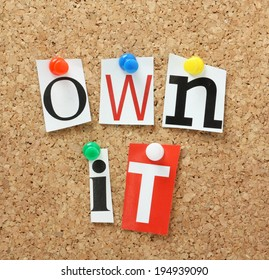 The phrase Own It in cut out magazine letters pinned to a cork notice board
