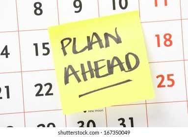 The phrase Plan Ahead written on a yellow sticky paper note and stuck on a wall calendar background