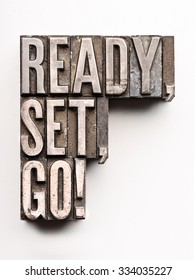 "The phrase ""Ready, set, go!"" in letterpress type. Cross processed, narrow focus."