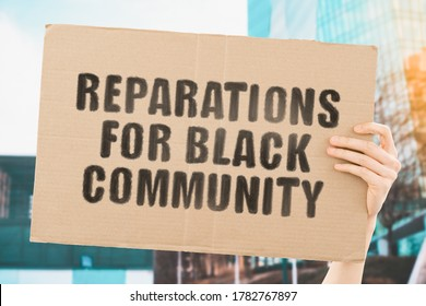 """The phrase """" Reparations for black community """" on a banner in men's hand with blurred background. Demand. Dishonest. Payment. Money. Slaves. Black people. Social inequality. Protest. Tough life"""