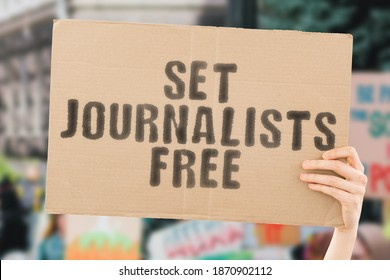 """The phrase """" Set journalists free """" on a banner in men's hand with blurred background. Freedom. Human rights. Free speech. Media. Power. Control. Government"""