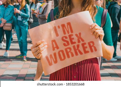 """The phrase """" I'm a sex worker """" on a banner in women's hand. Girl holds a cardboard with an inscription. Female. Job. Feminism. Profession. Business. Money. Earnings"""